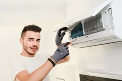 handsome young man electrician installing air conditioning in client house