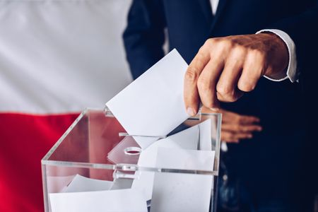 Man throwing his vote into the ballot box. Polish flag in the background.